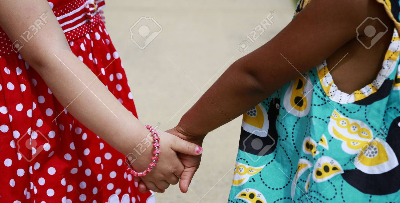 Diversity: Caucasian and African - American little girls holding hands - 57828763