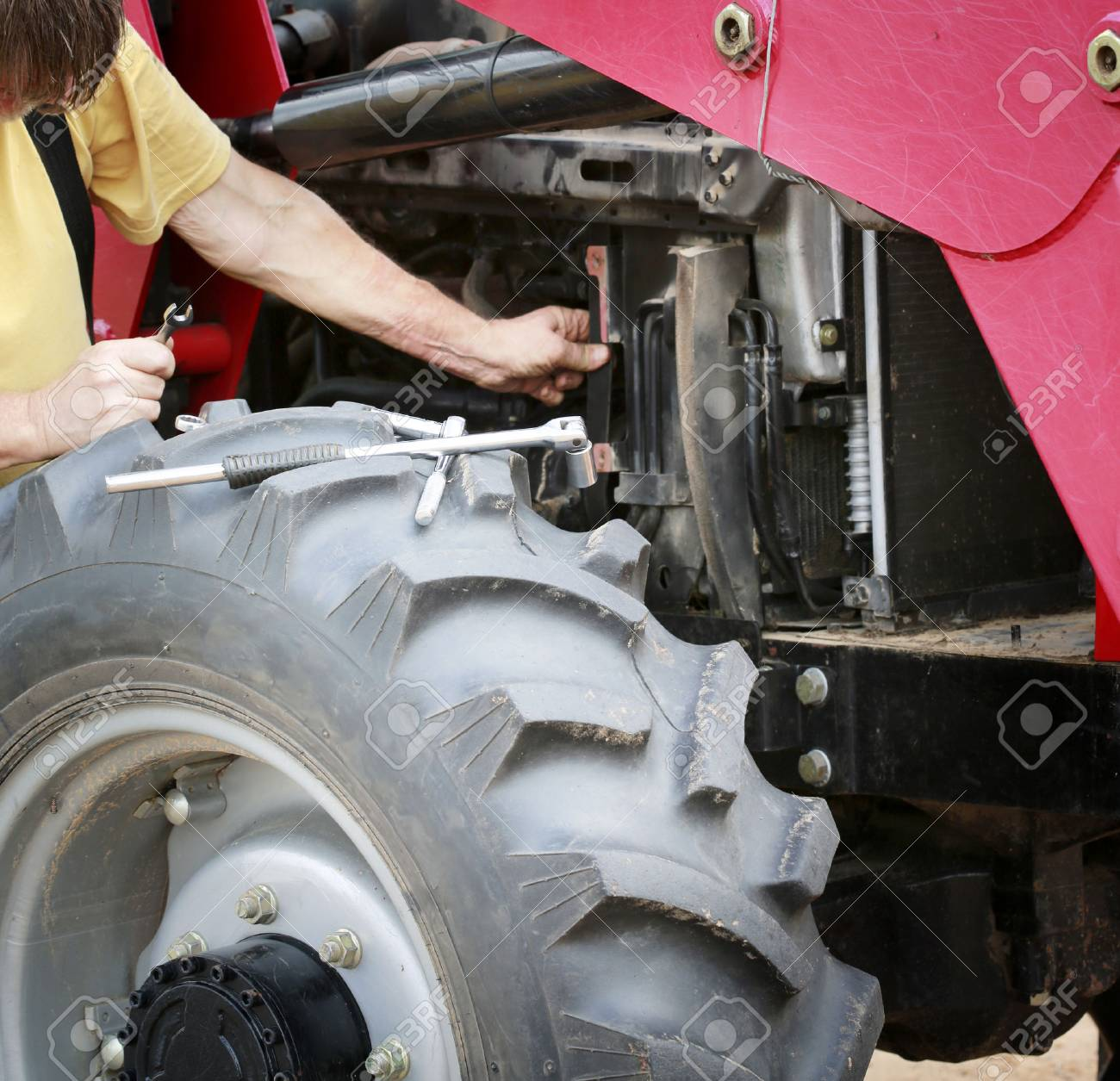 Man repairs large red tractor with focus on tools and front wheel - 78711435
