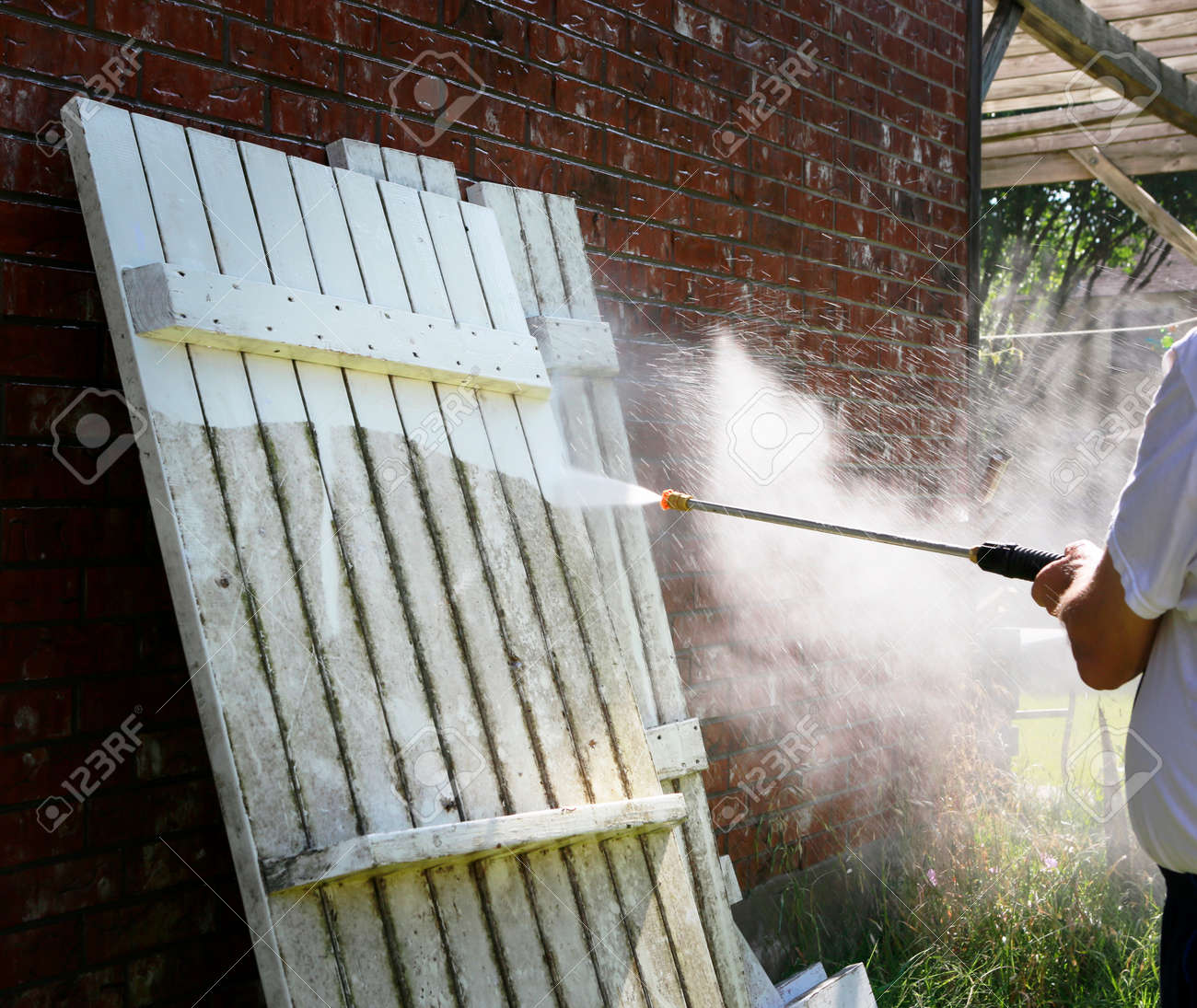Cleaning very dirty picnic table with power washing machine. High pressure water cleaning of white wooden surface on backyard. - 146159000