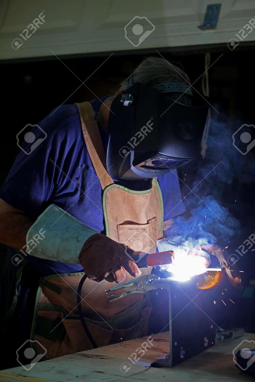 Welding. Welder is welding metal part - 147994571