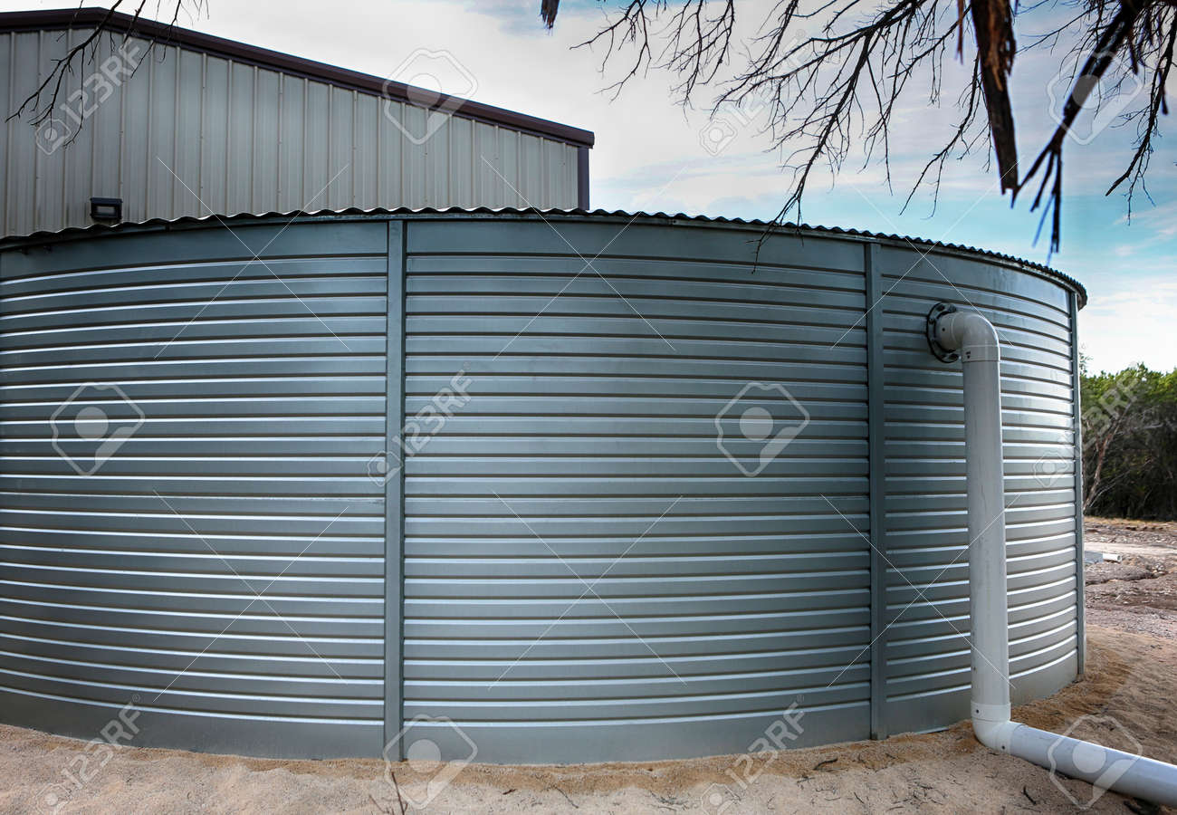 Close up of Large rain water tank, ecology friendly, in front of metallic building. - 152816428