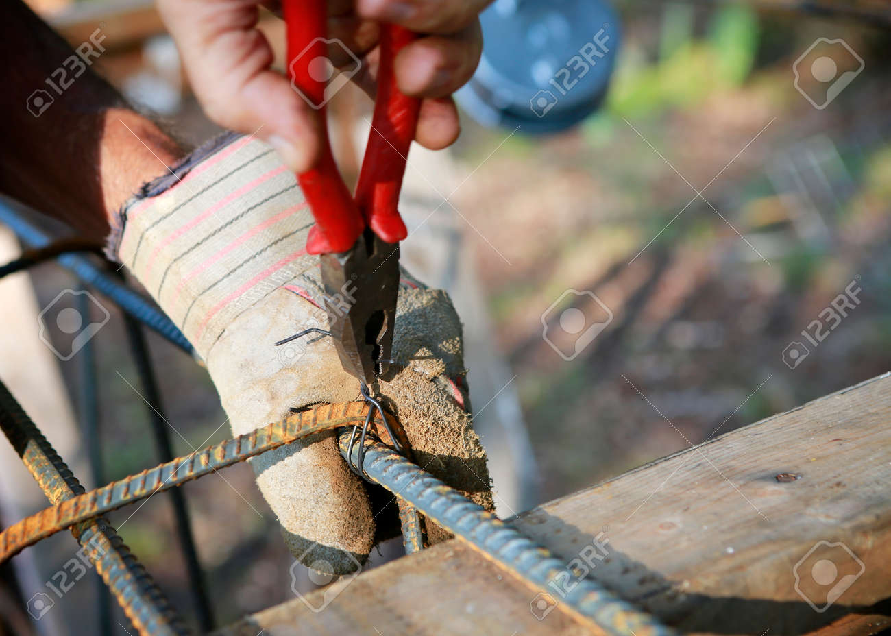 Attaching the rebars to each other. Worker's hands fasten the reinforcement with wire. Close up, selective focus. - 156159684