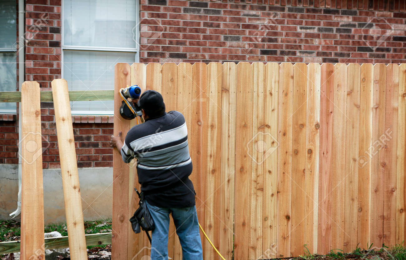 Building a new fence. Worker using a nail gun to attach wood pickets to the rail for new fence. - 159060797