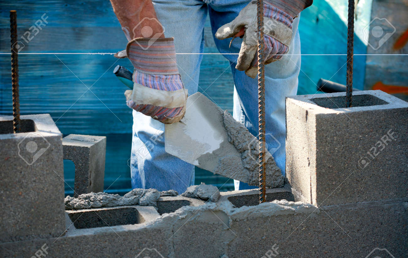Construction site: building wall of concrete block. Mason in laying concrete blocks - 169484706