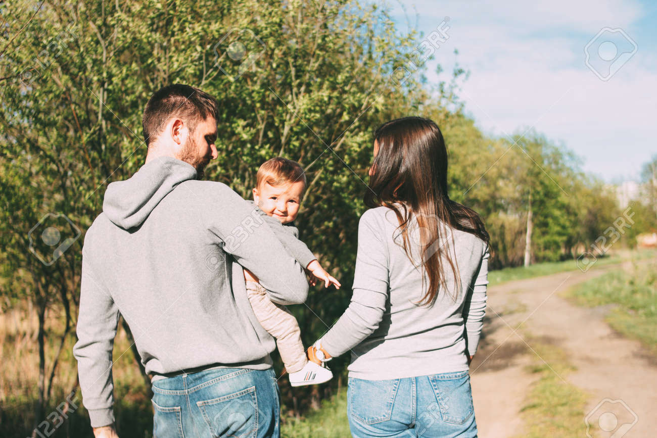 Happy family with cute baby boy walking on road outdoors, sensitivity to the nature concept - 125699957