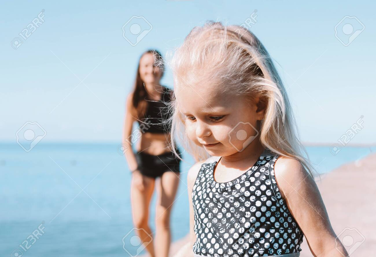Little cute girl running to fit mom on the beach, healthy lifestyle, sport family - 129801829