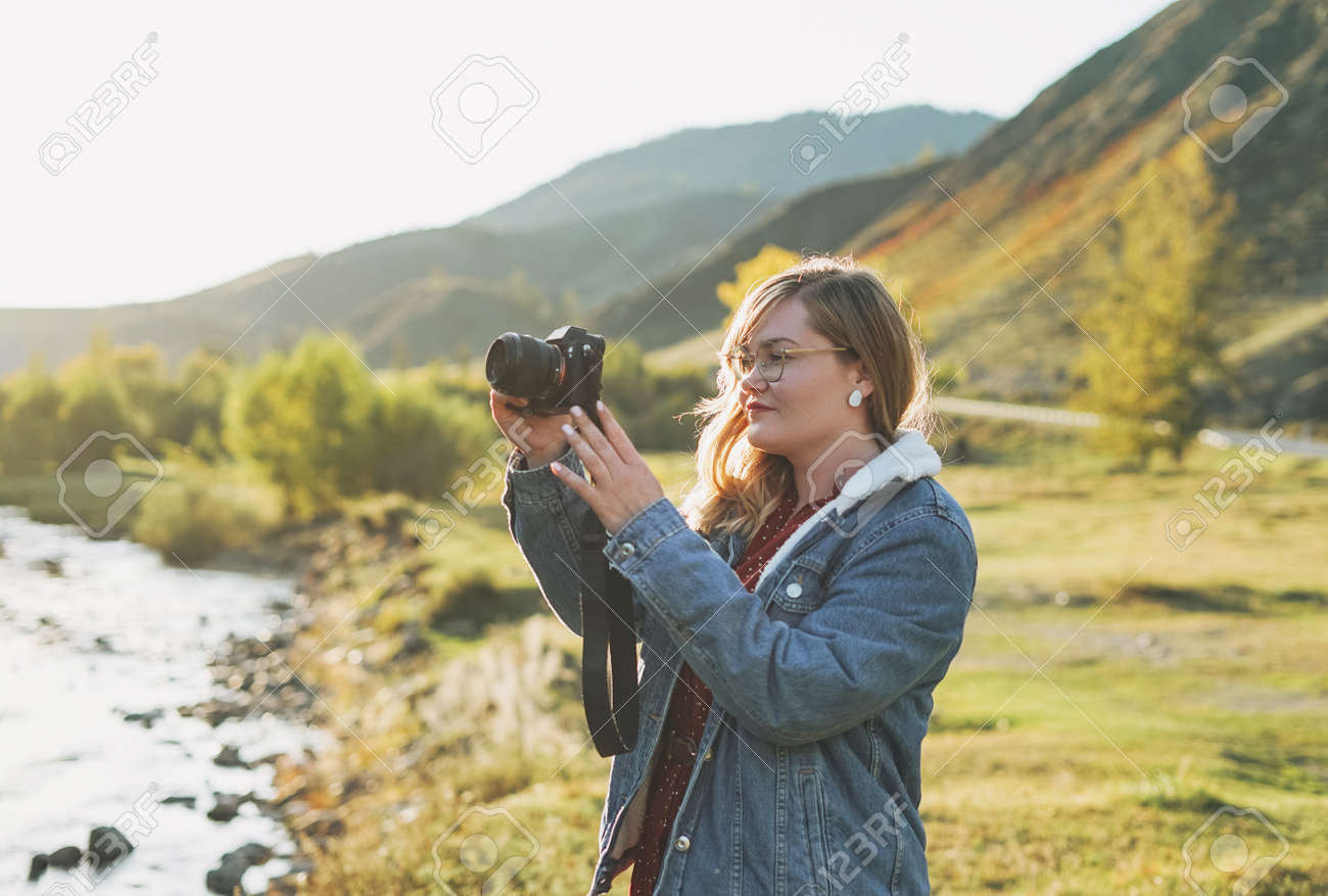 Beautiful smiling blonde young woman traveler with photo camera in hands, trip to the mountains - 157096821