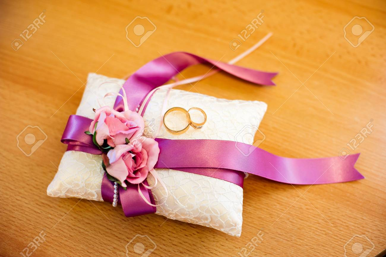Golden Wedding Rings On Decorated Little Pillow With Purple Ribbons ...