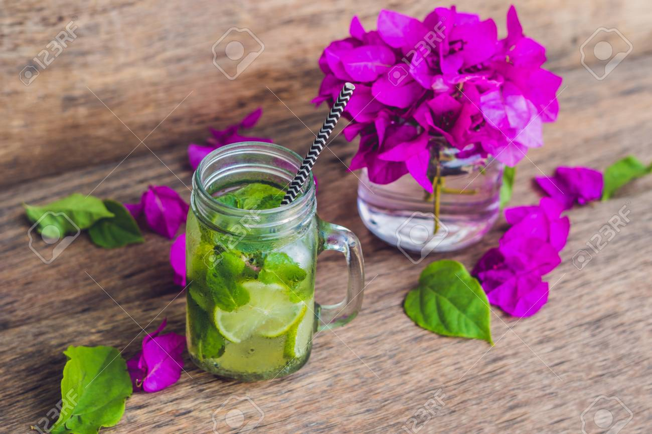 Spring Purple Flowers And Spring Mojito Drink On An Old Wooden