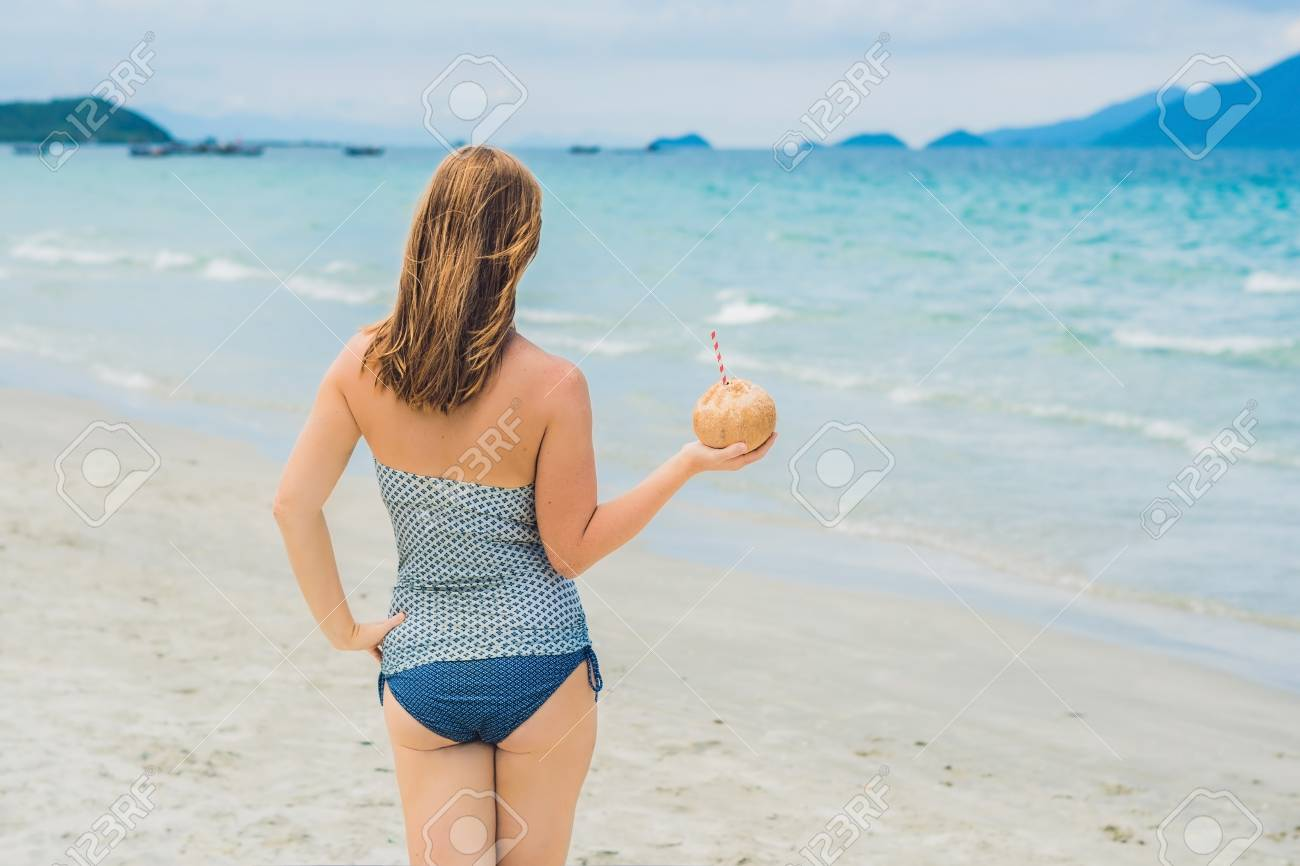 Young woman drinking coconut milk on beach  Dream scape Escape