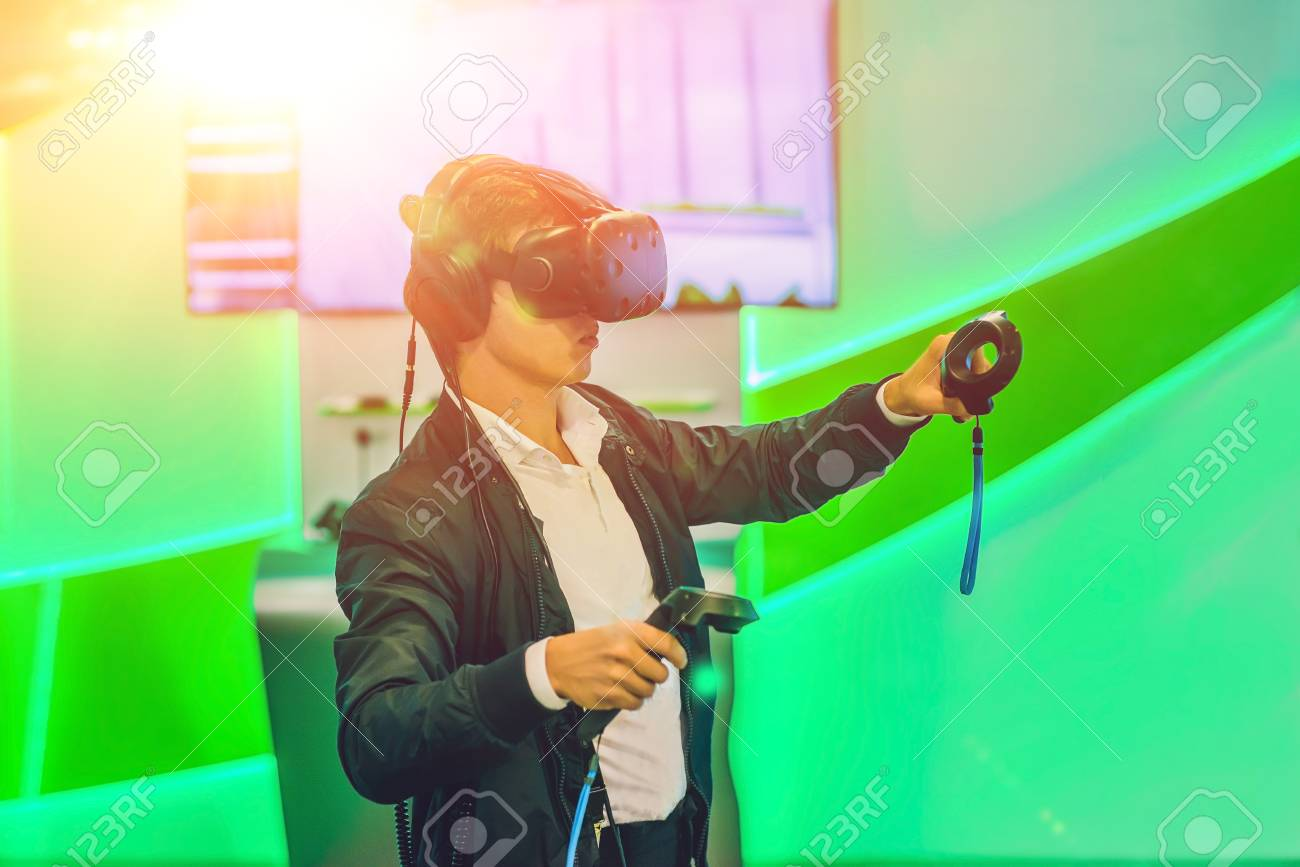 f6104c23124 Stock Photo - Young man playing video games virtual reality glasses.  Cheerful man having fun with new trends technology - Gaming concept.