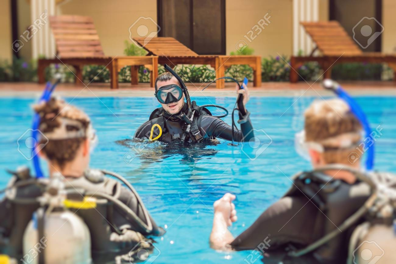 Diving instructor and students. Instructor teaches students to dive. - 93276783