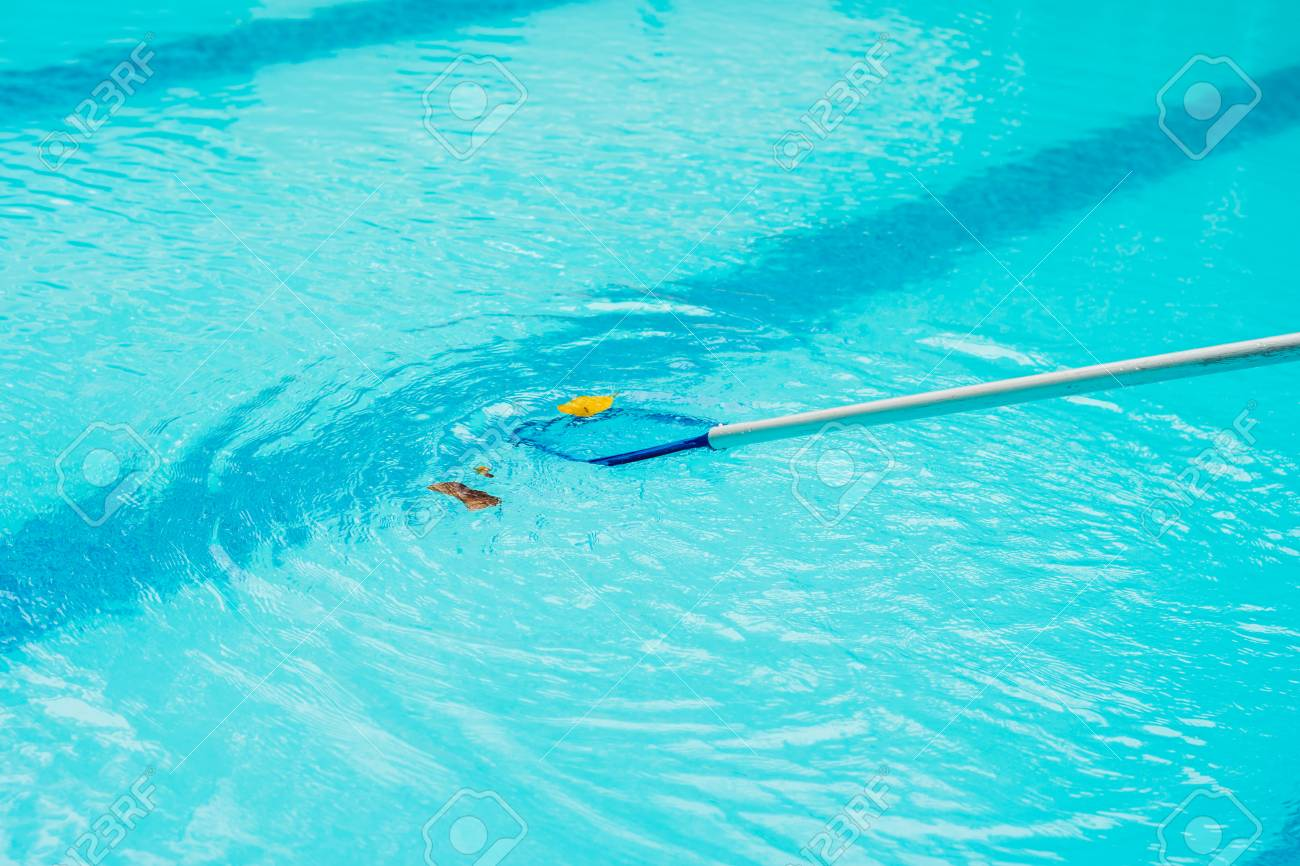 Cleaning swimming pool with cleaning net in the morning.