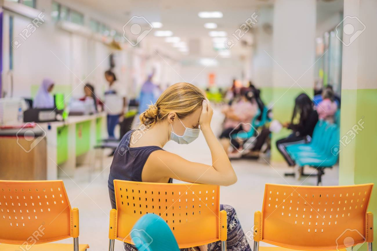Young woman sitting in hospital waiting for a doctors appointment. Patients In Doctors Waiting Room - 118476565