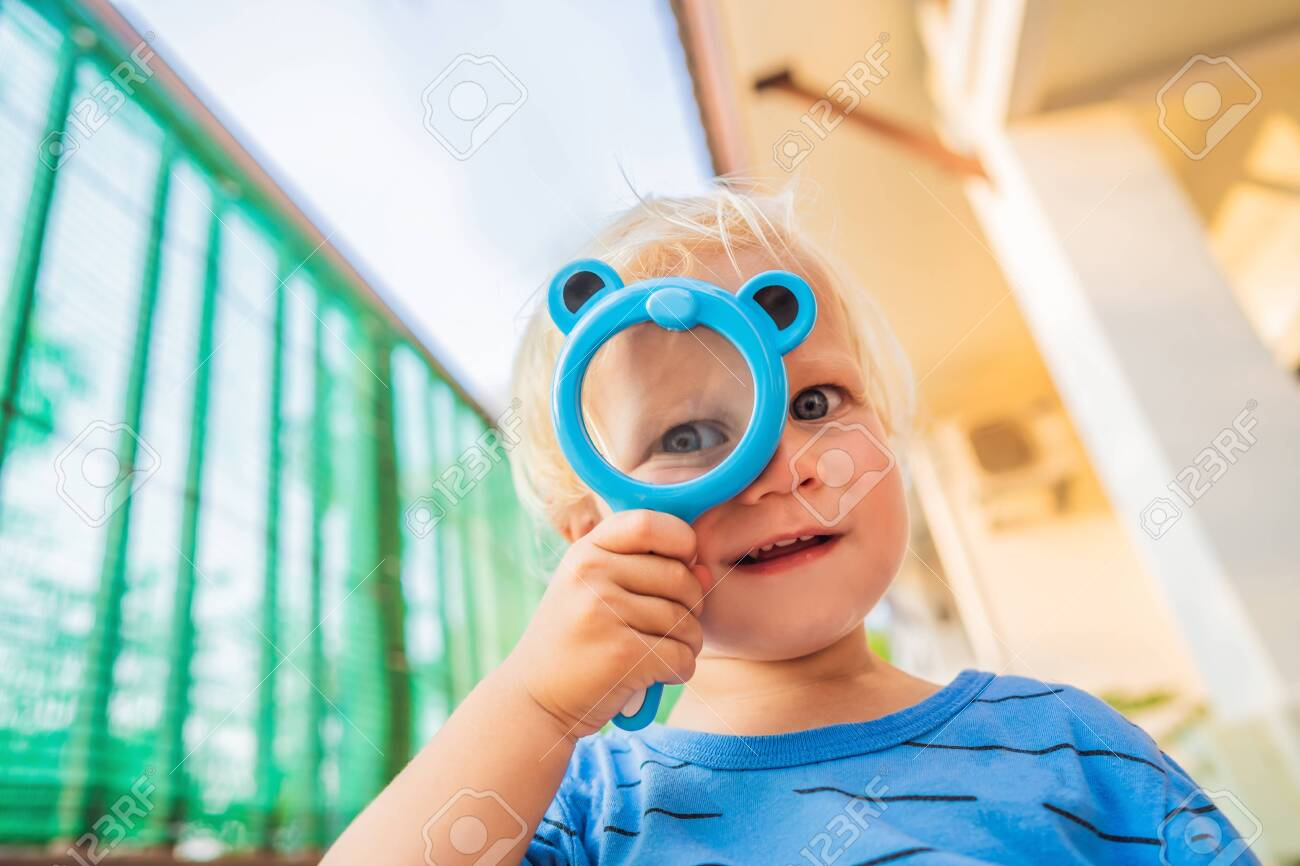 Boy looking in a magnifying glass against the background of the garden. Home schooling - 121256307