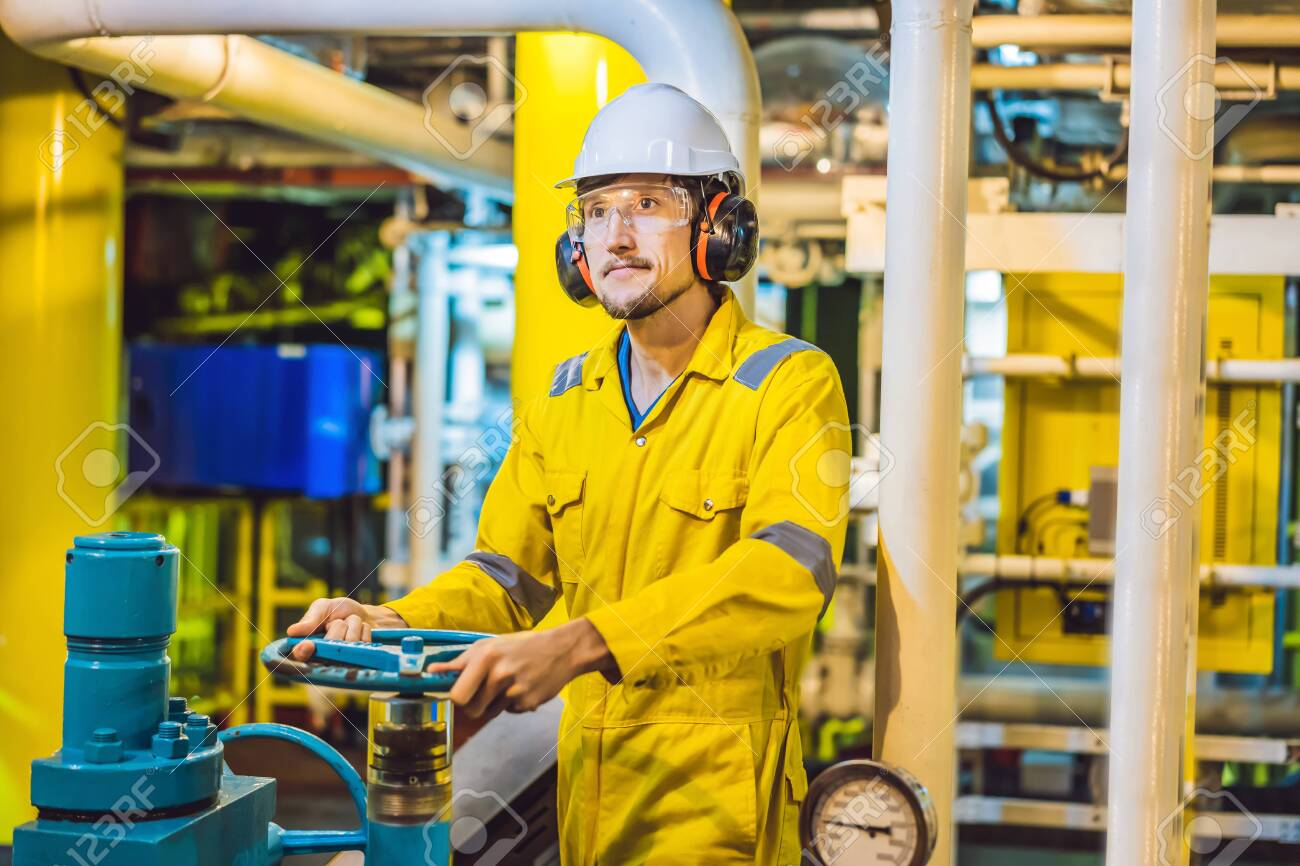 Young man in a yellow work uniform, glasses and helmet in industrial environment,oil Platform or liquefied gas plant - 122691405