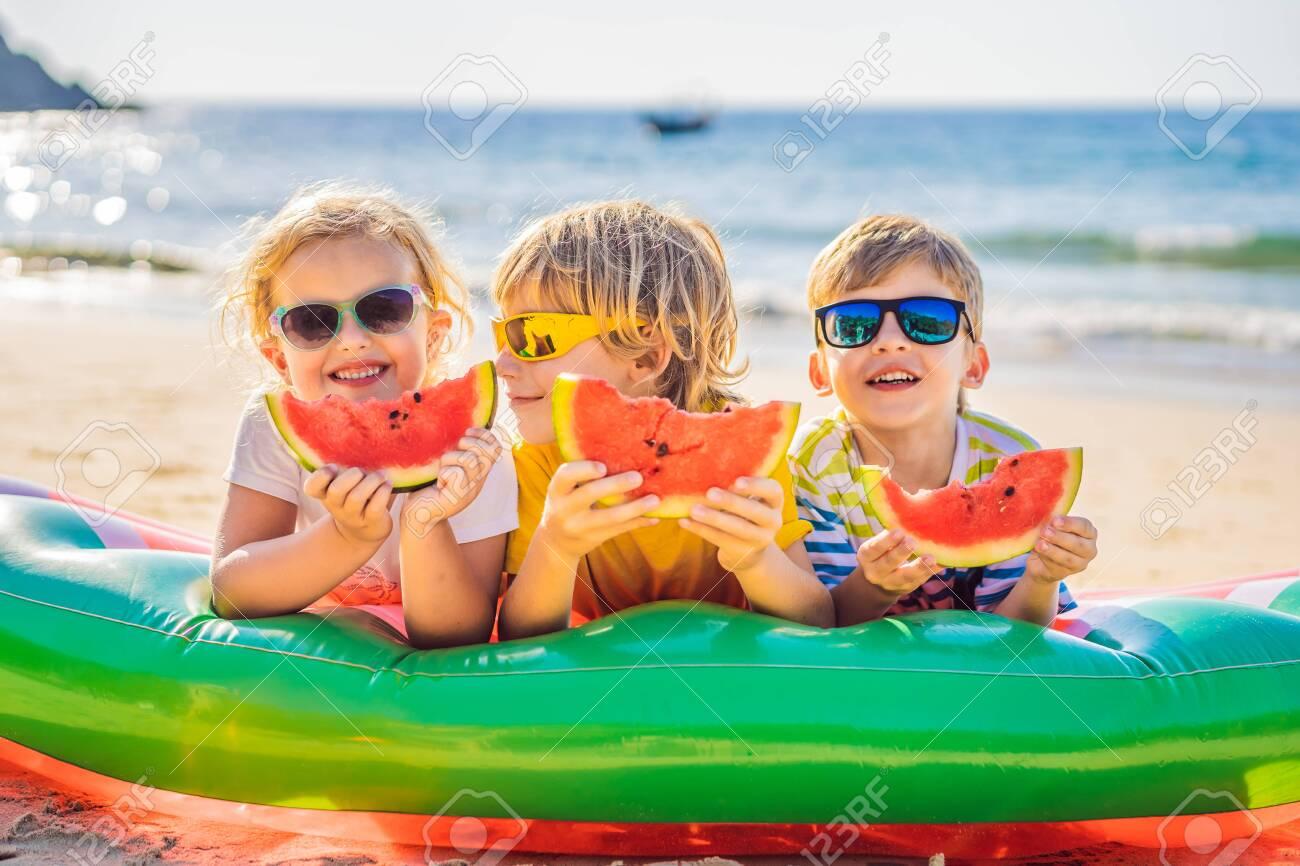 Children eat watermelon on the beach in sunglasses - 123052701