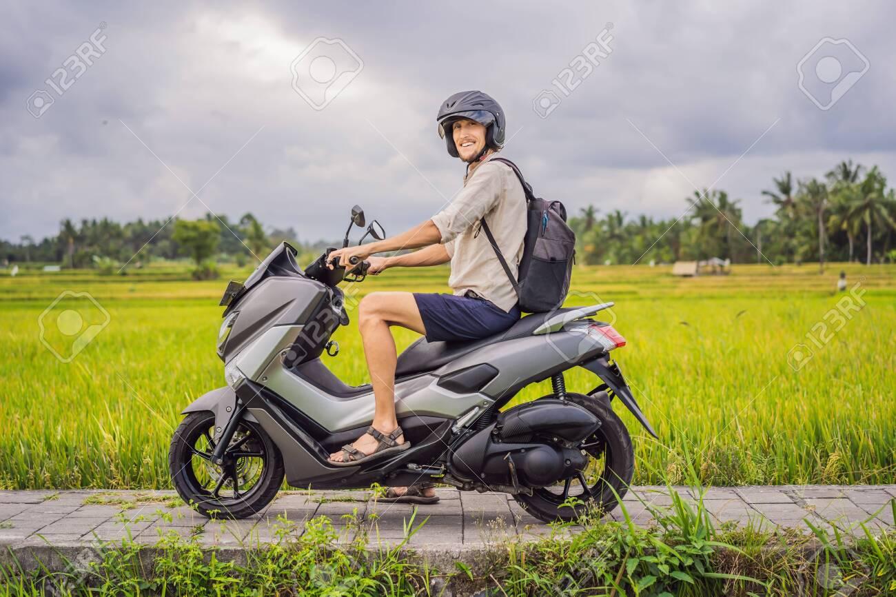 Male traveler on a bike among a rice field. Tourist travels to Bali - 133031242