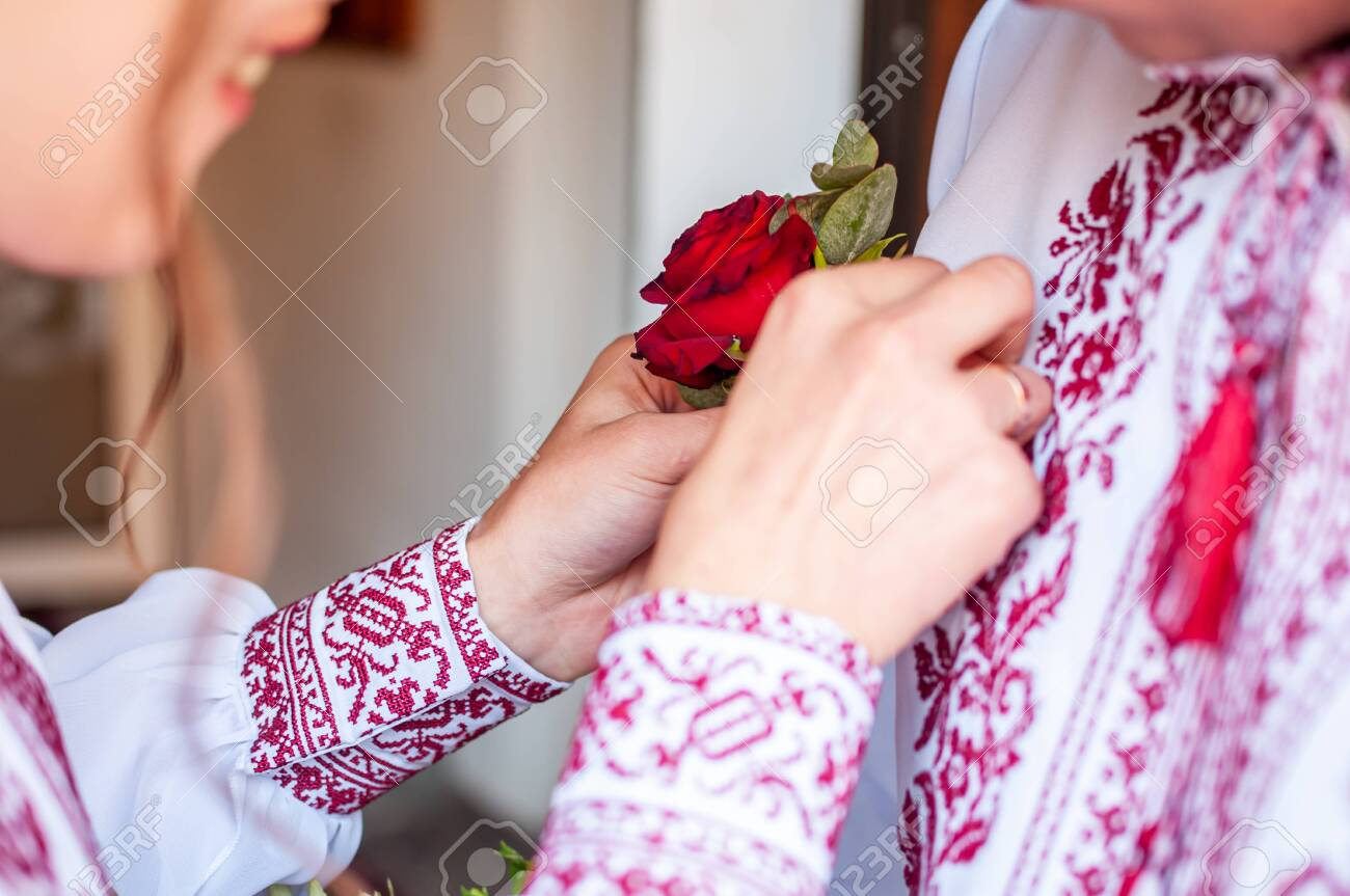 Girl dresses groom boutonniere on the shirt - 146129884