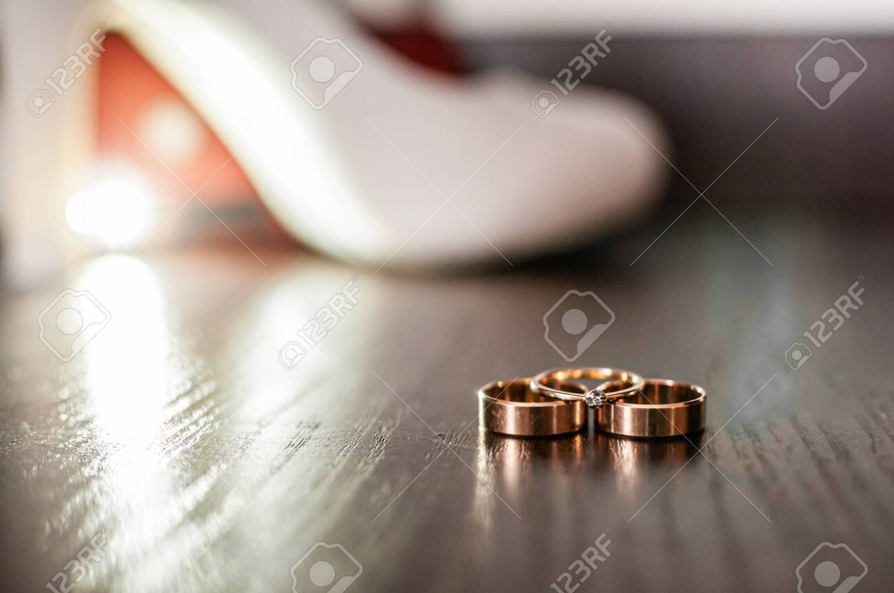 Three gold wedding rings and white high heel shoe on the table - 146237000
