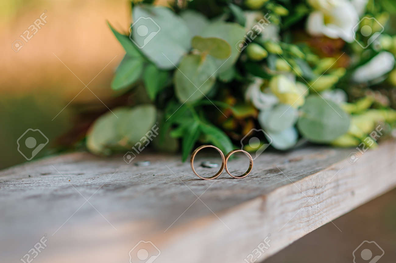 Wedding rings on a wooden stand against the background of the bride's bouquet - 165061829