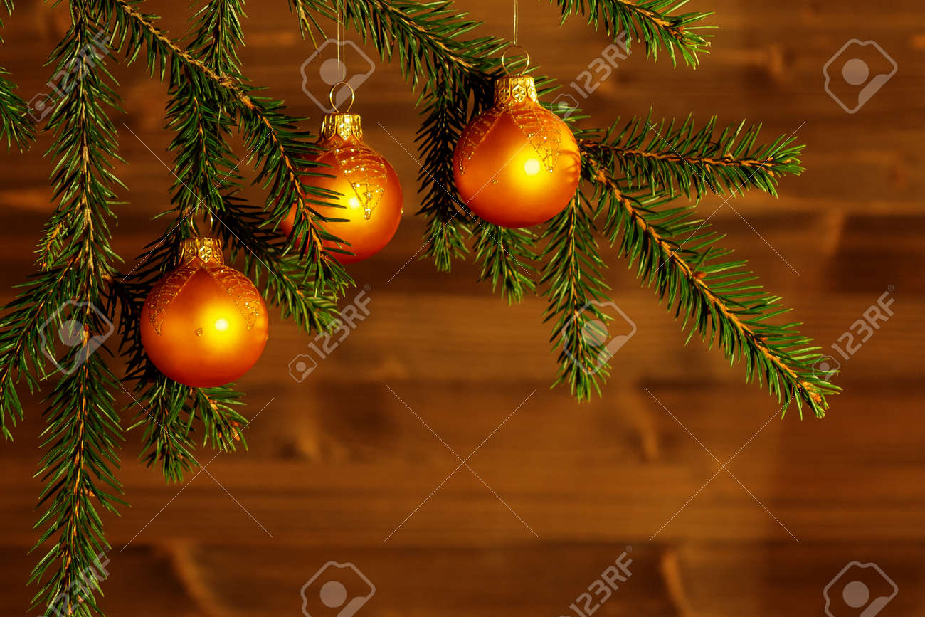 Orange Christmas ornaments on spruce branches on the background of a wooden wall. New Year or Christmas background - 122526335
