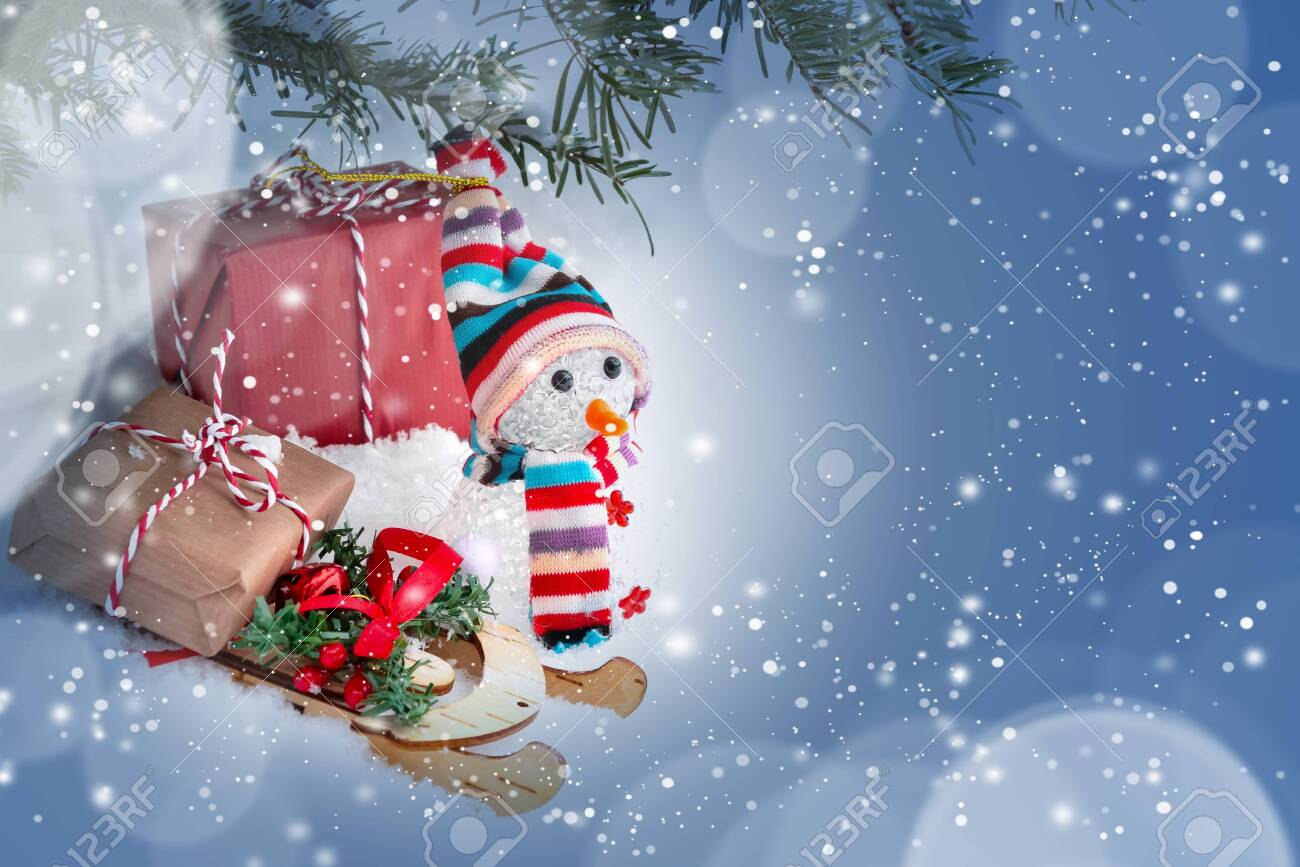 Christmas composition under the Christmas tree - a snowman, boxes with gifts on a sled and other decorations, place for text, copy space - 129337672
