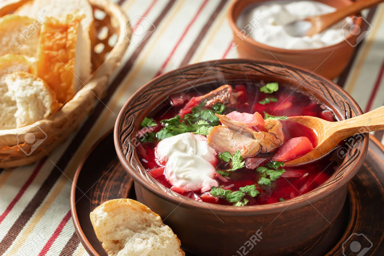 Freshly cooked hot homemade borscht - traditional dish of Russian and Ukrainian cuisine in earthenware dishes with bacon, bread, sour cream and garlic - 170577188