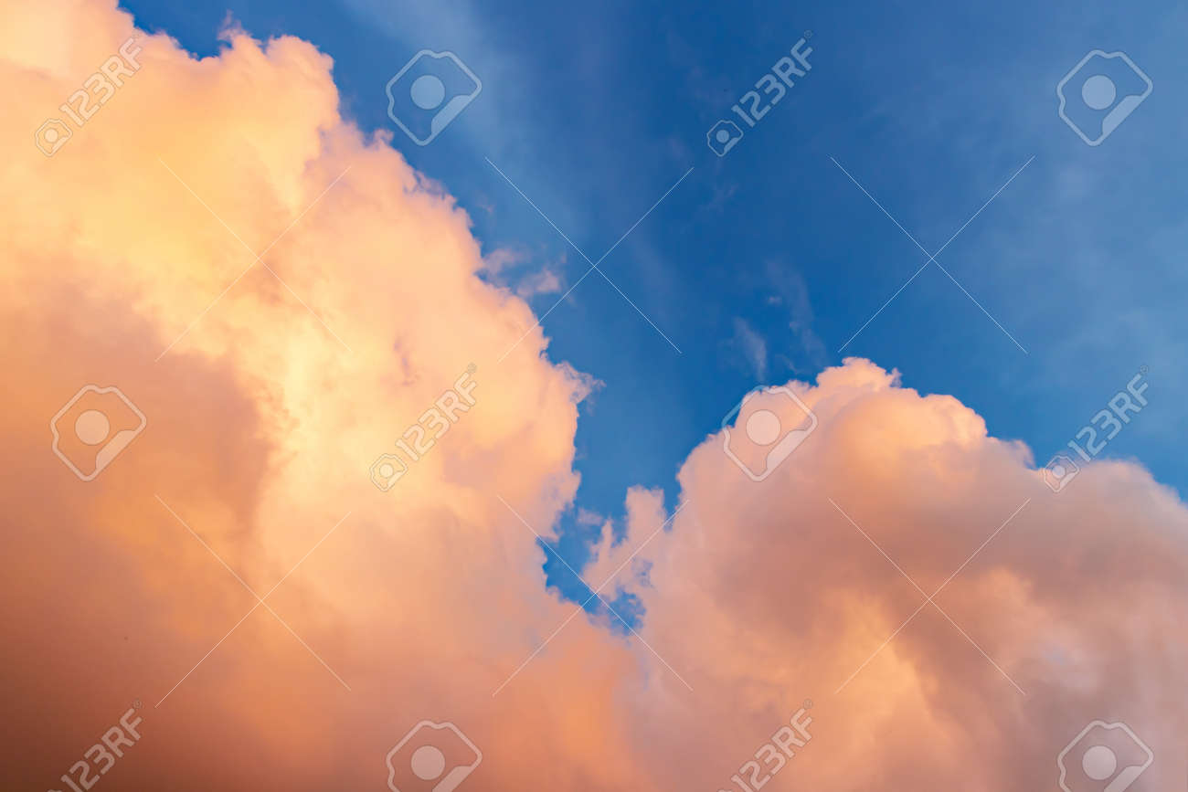 Beautiful cloudscape - pink-orange clouds in the rays of the sun against the blue sky - 170577196