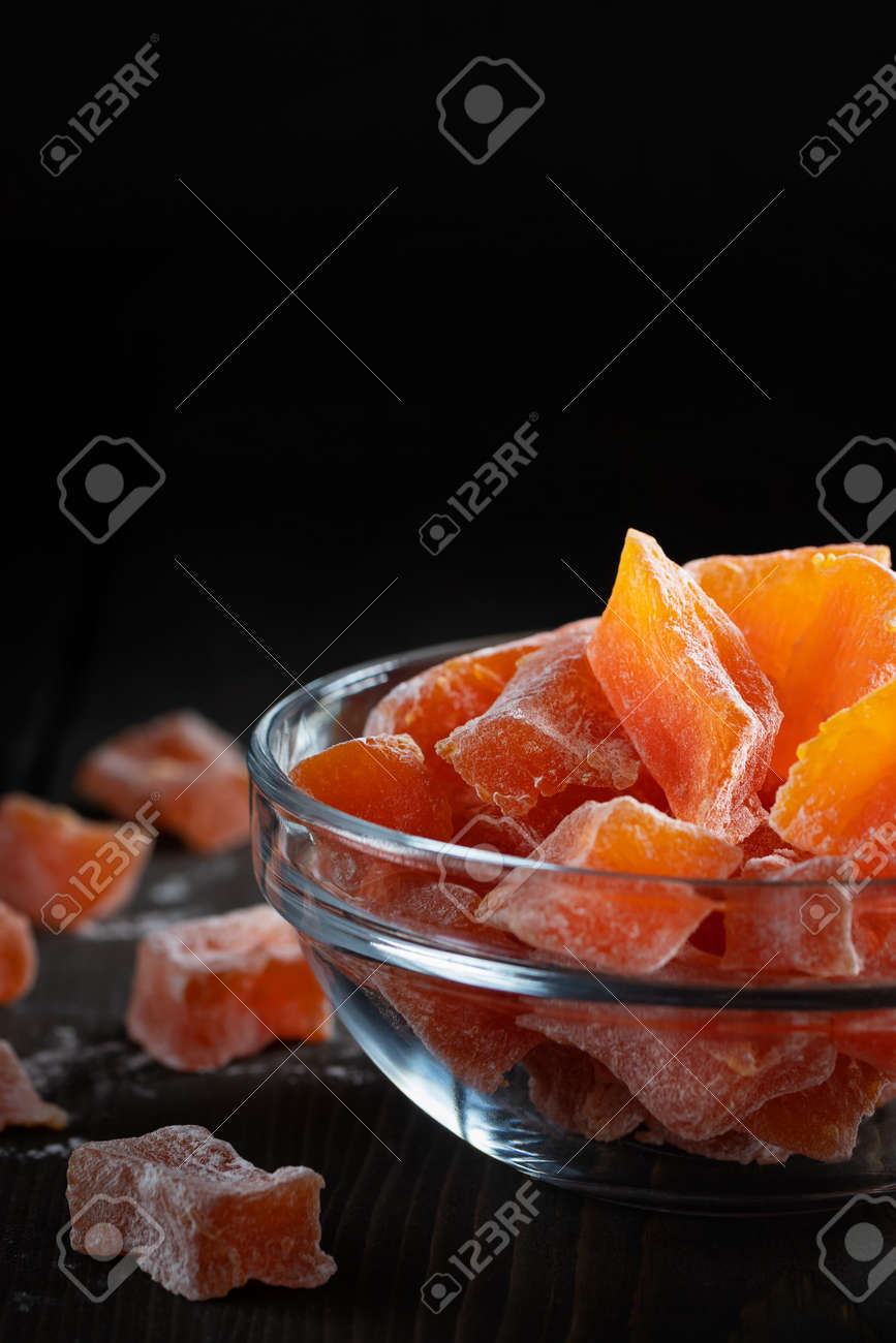 Natural farm homemade candied pumpkin fruits sprinkled with powdered sugar in a glass bowl on a wooden table - 170577239