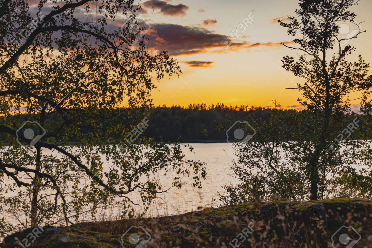 Sunset on a lake with rocky shores in Karelia - 170095669