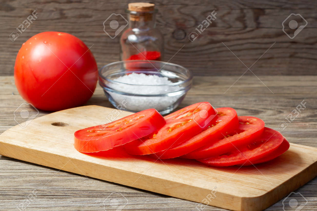 Tomato sliced into round slices on a wooden cutting board - 170504905