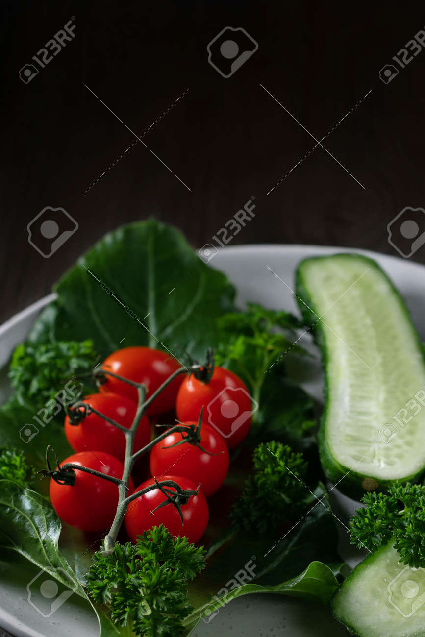 Fresh vegetables and herbs in a plate on a wooden table. Concept of vegetarianism and healthy eating. Copyspace. - 171232789