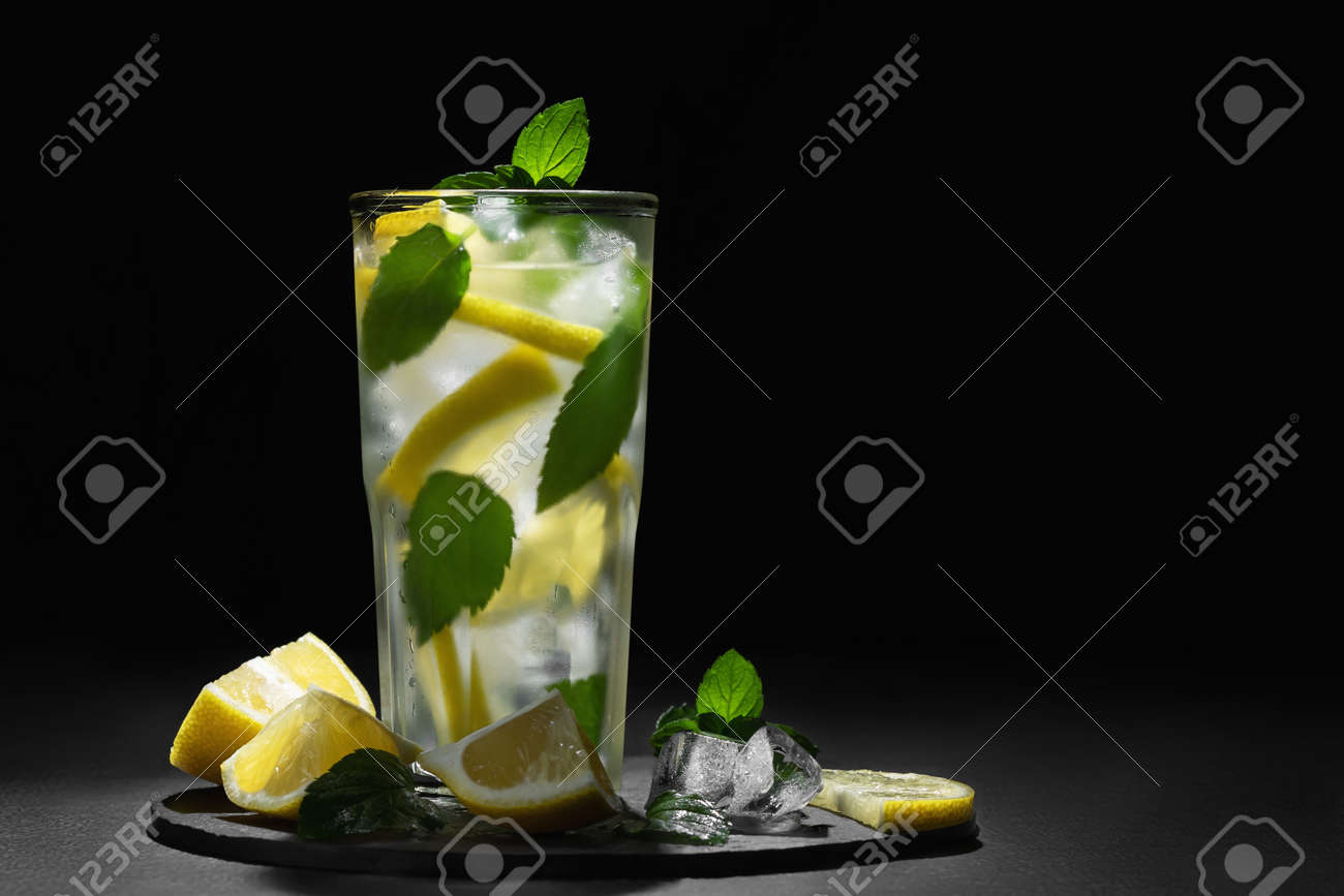 Fresh homemade cocktail with lemon, mint and ice on a dark background - 171232818