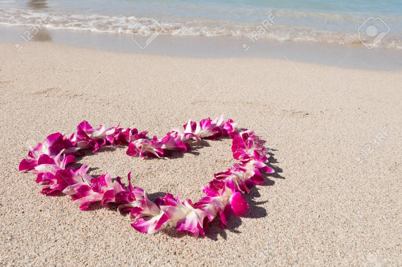 Orchid flower garland necklace in love heart shape on white sea orchid flower garland necklace in love heart shape on white sea sand beach romantic couple izmirmasajfo Images