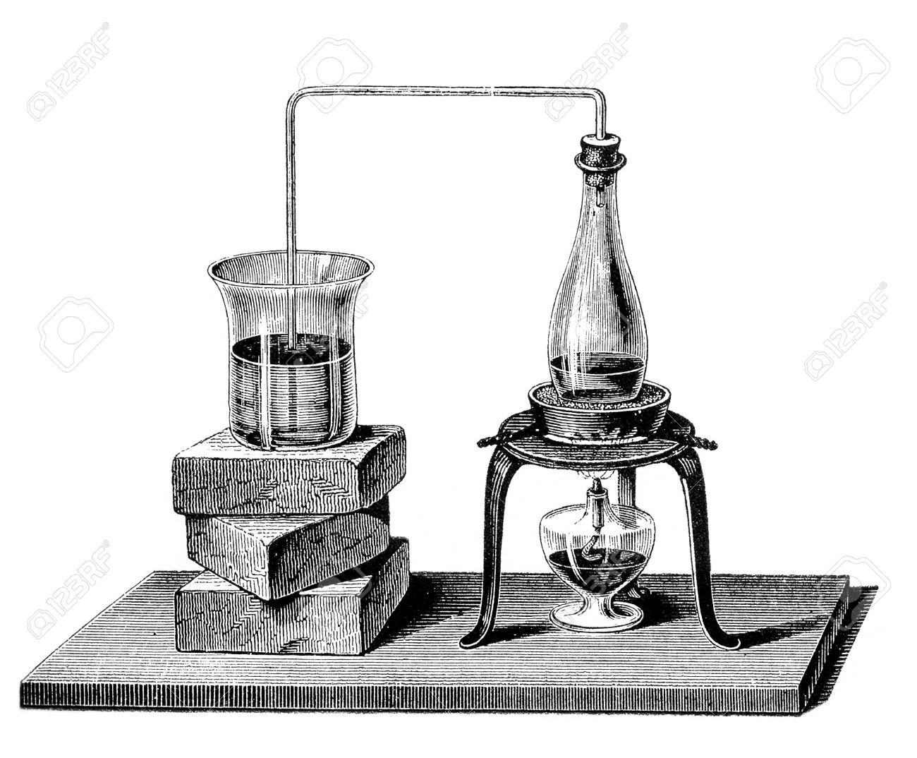 The bended glass pipe canalizes vapor from the  boiling water in the closed flask to the receiving glass on the left, causing the water inside to boil too Stock Photo - 26965830