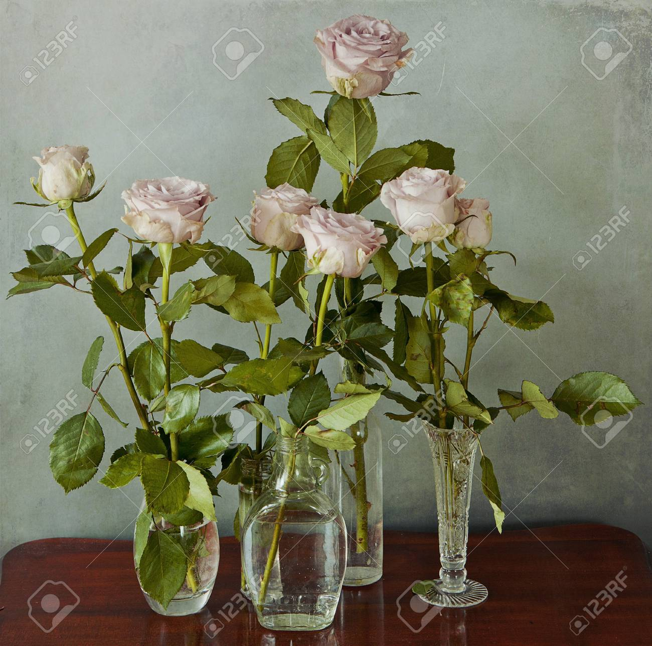 Arrangement of pink roses in glass vases on a wooden table and arrangement of pink roses in glass vases on a wooden table and grunge background stock photo reviewsmspy