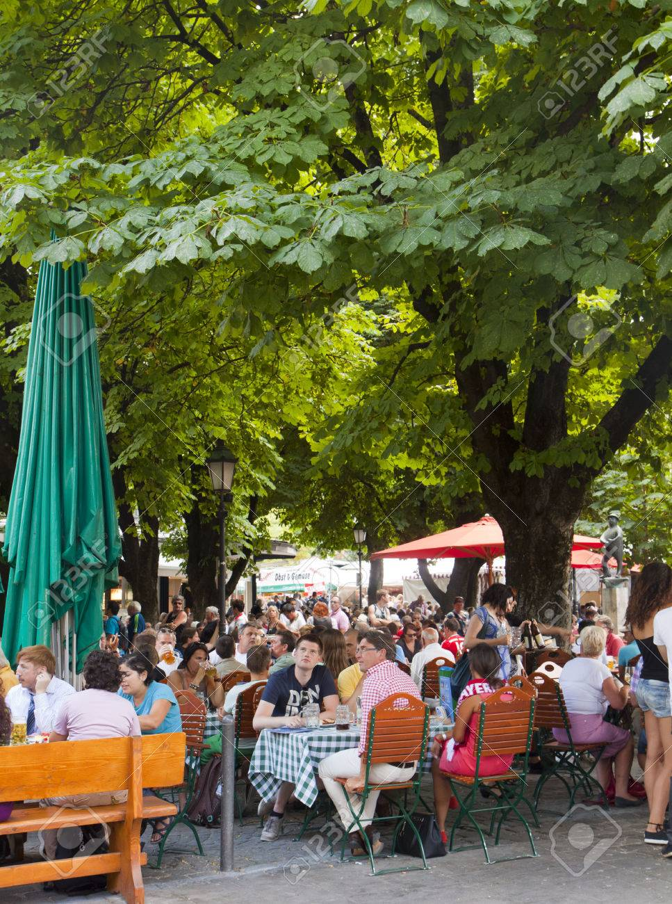 people seat and enjoy beer and food at a open air restaurant at Viktualien Markt in Munich Stock Photo - 35784034