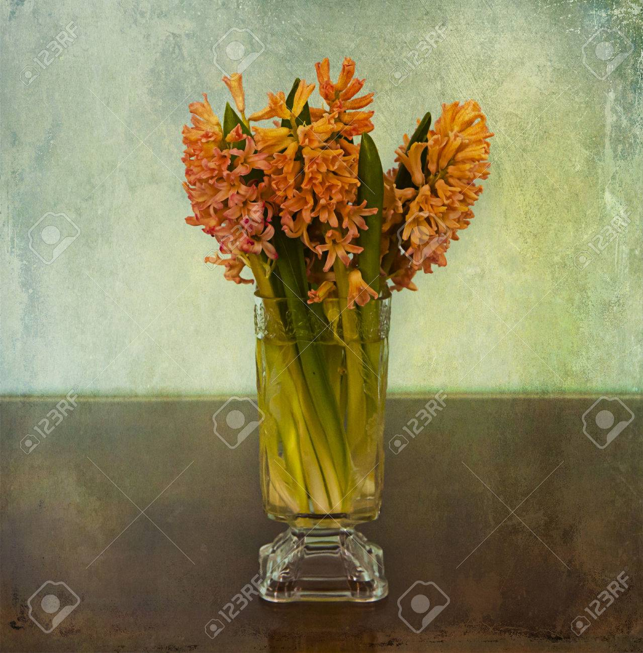 Elegant and minimalistic glass vase with a bouquet of pink  hyacinths on grunge textured background Stock Photo - 40938699
