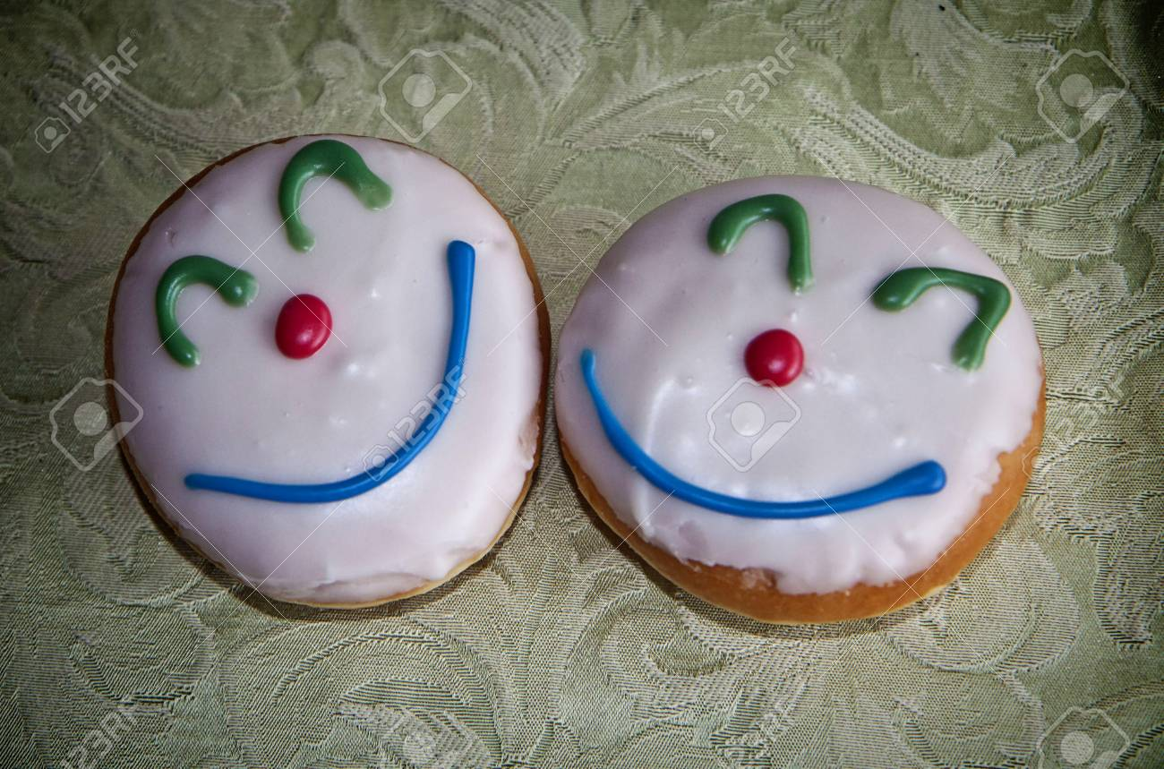 Carnival doughnuts with glazed cream and clown face decoration Stock Photo - 72831104