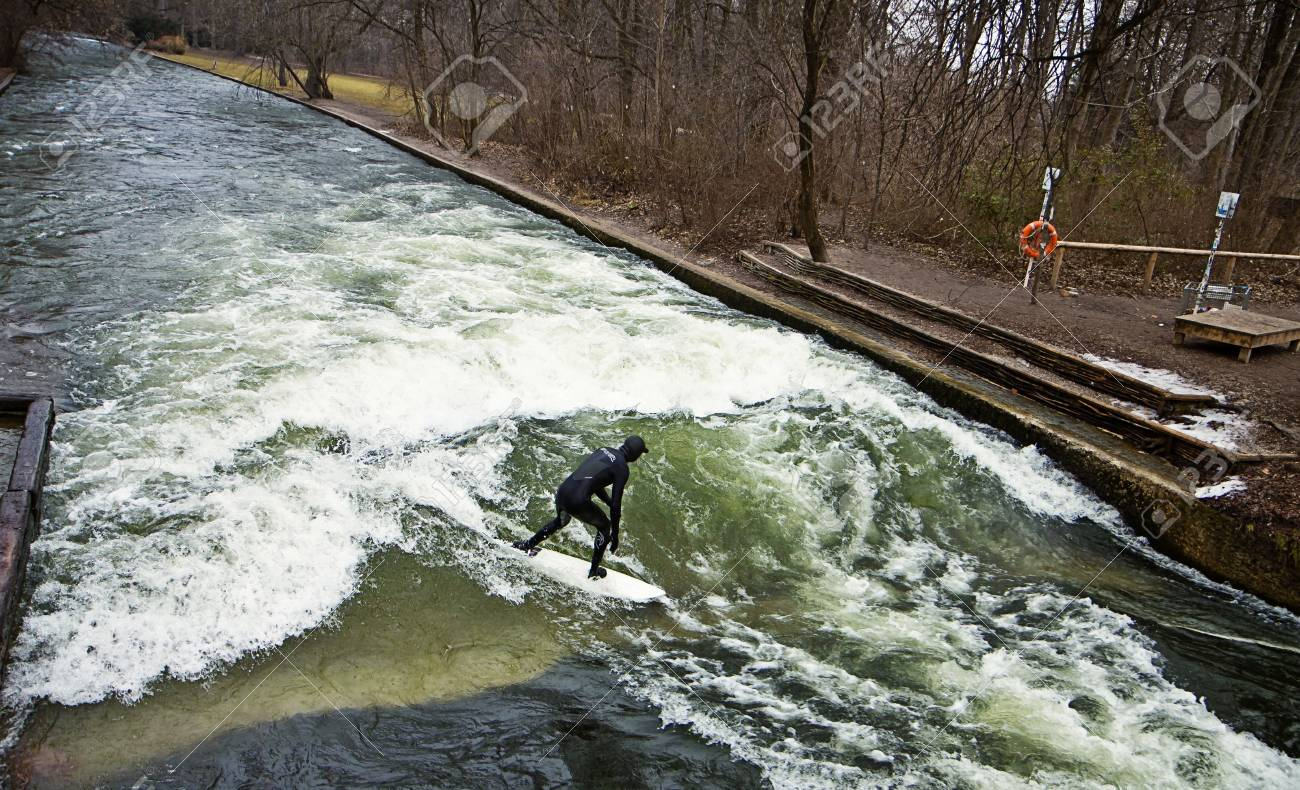 Munich, surfer riding the artificial wave on the Eisbach, small river across the Englischer Garten, in a freezing February morning Stock Photo - 73736091