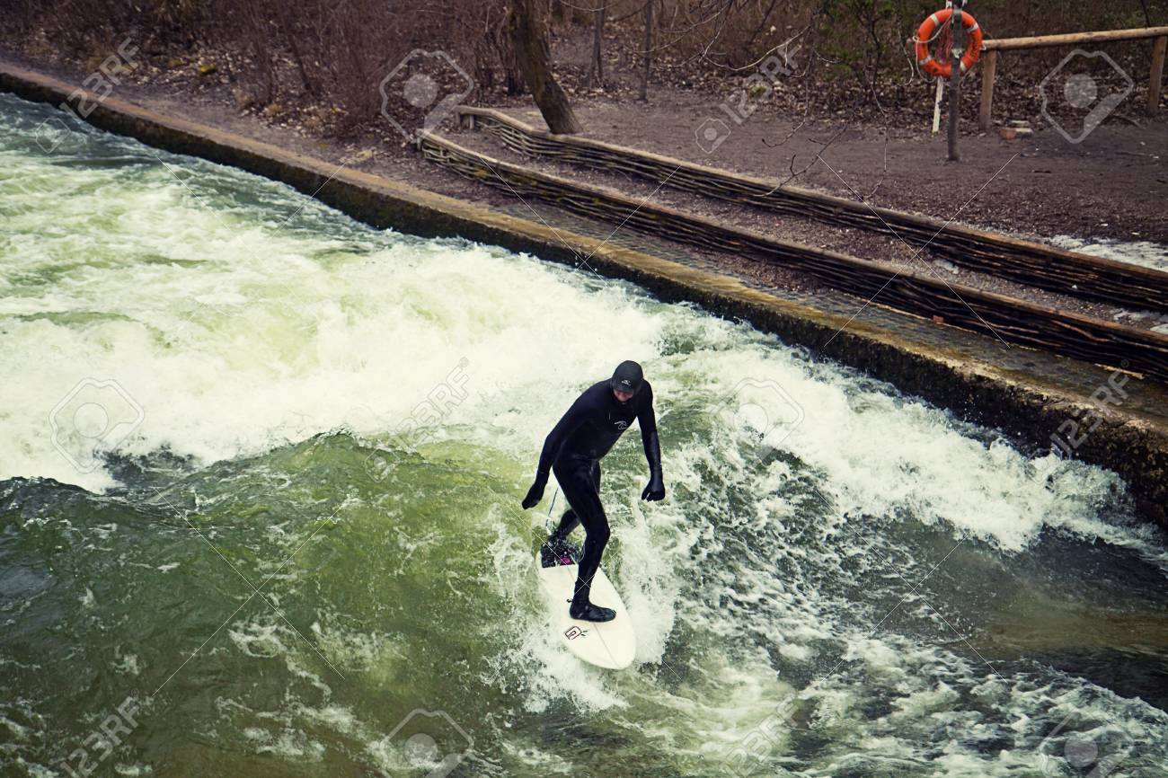Munich, surfer riding the artificial wave on the Eisbach, small river across the Englischer Garten, in a freezing February morning Stock Photo - 73736090