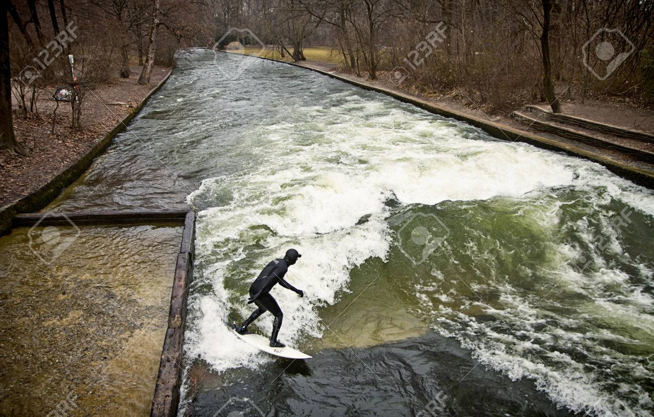 Munich, surfer riding the artificial wave on the Eisbach, small river across the Englischer Garten, in a freezing February mornng Stock Photo - 73736089