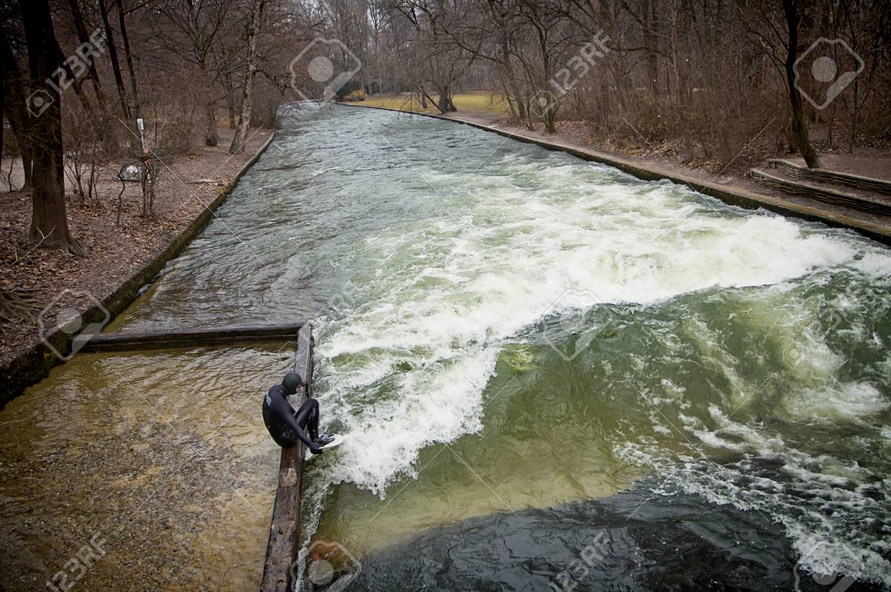 Munich, English Garden - solitary surfer prepares to surf the artificial wave of the Eisbach river in a freezing February morning with temperature below 0 (32 F) Stock Photo - 73736099