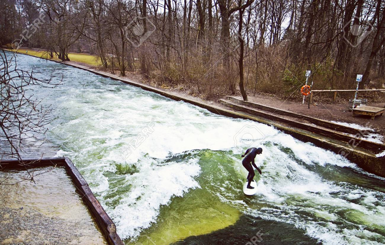 Munich, surfer riding the artificial wave on the Eisbach, small river across the Englischer Garten, in a freezing February morning Stock Photo - 73736098
