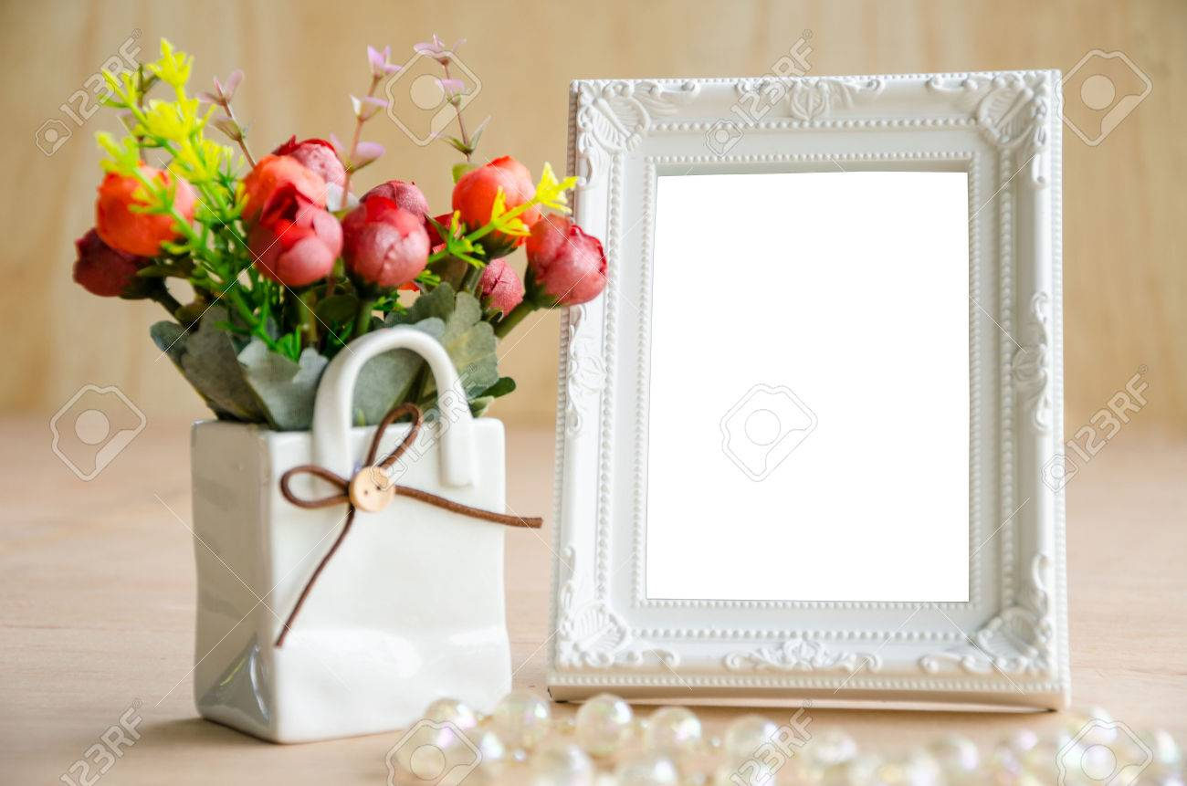 Flowers vase and vintage white picture frame on wooden desktop, clipping path - 42047455