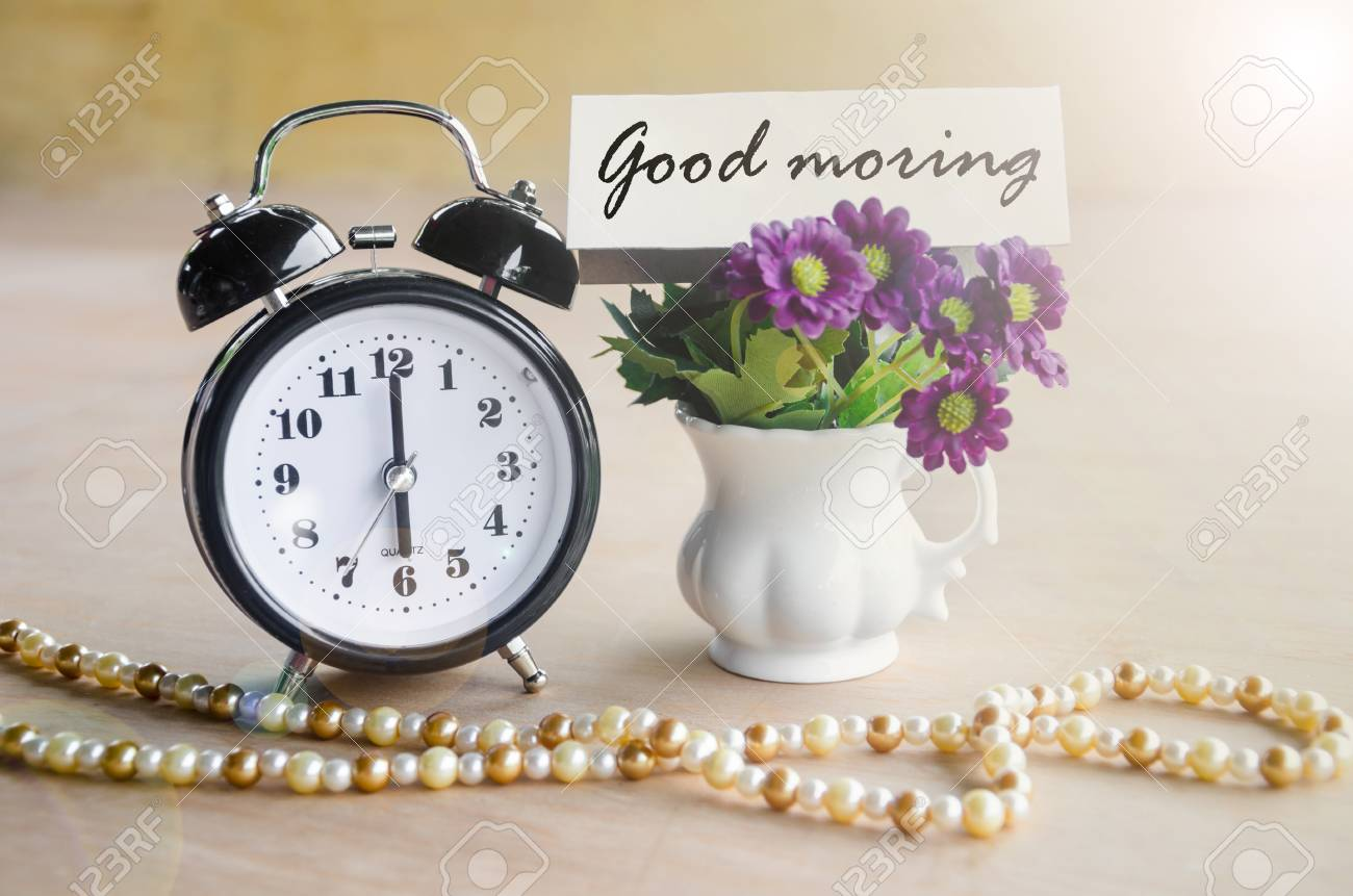 alarm clock and good morning tag with violet flower on wooden