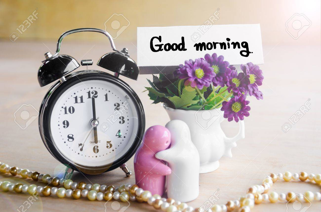 flowers in a ceramic pots with purple vintage alarm clock and