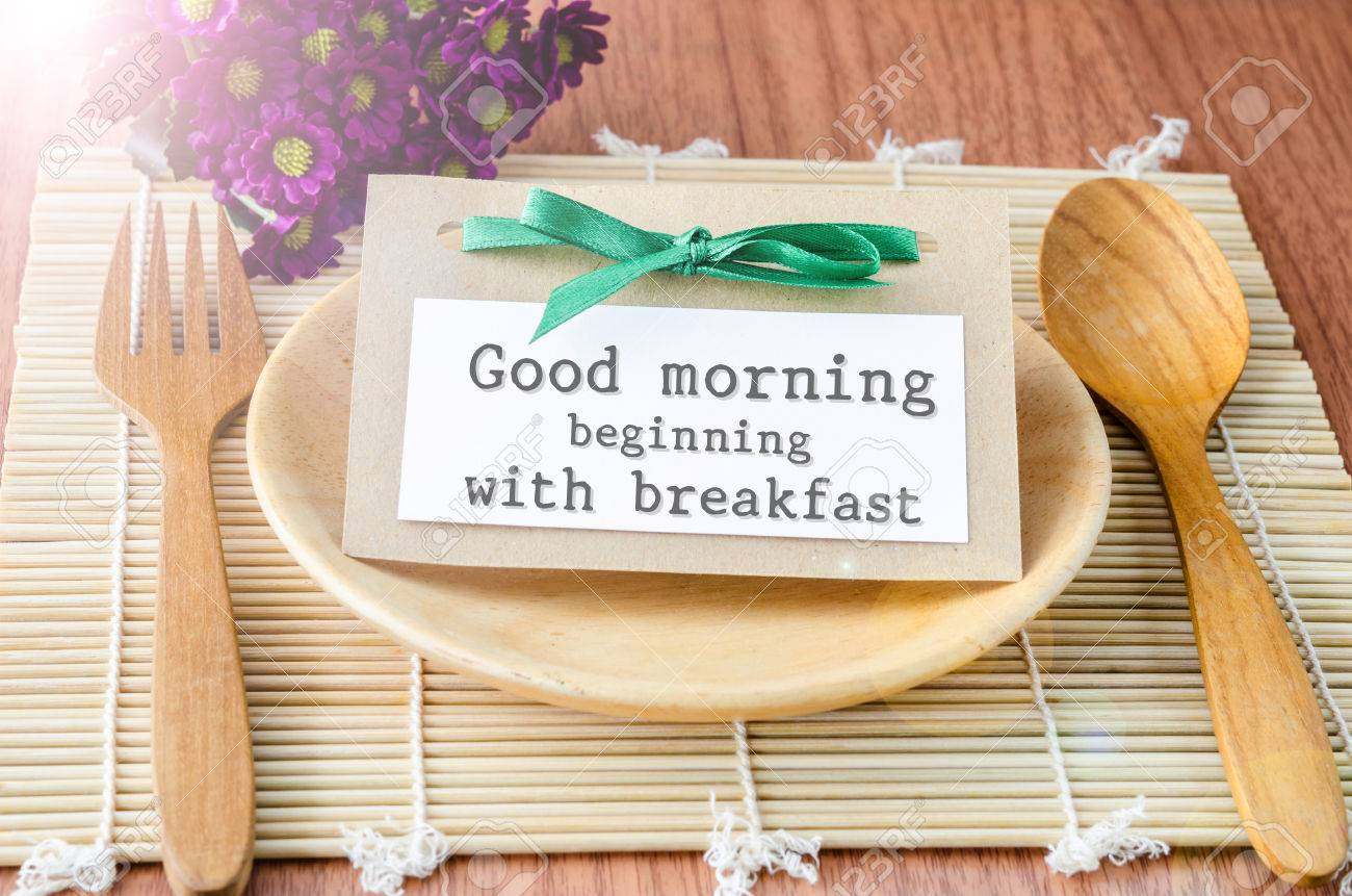 Good Morning Beginning With Breakfast Tag On Dish Spoon With Flower On Wooden Background Stock