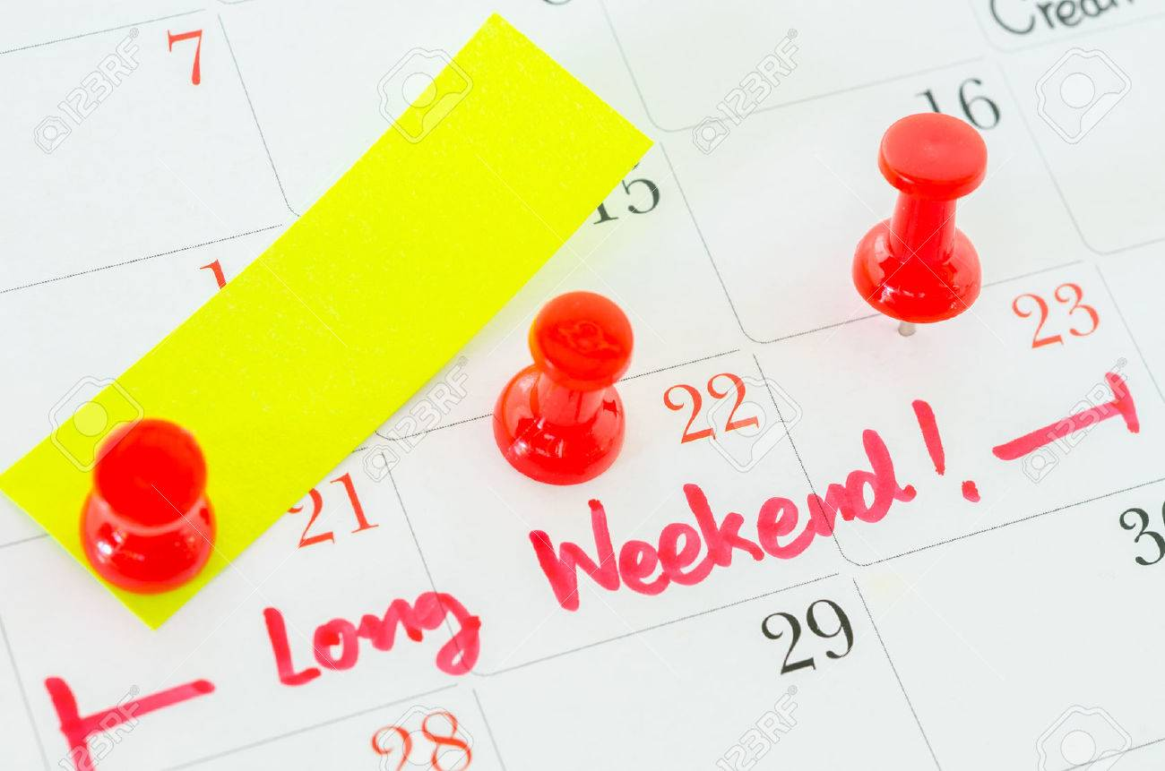 Concept image of a Calendar with a red push pin. Closeup shot of a thumbtack attached. The words Long Weekend written on a white calendar to remind you an important appointment. - 48174645